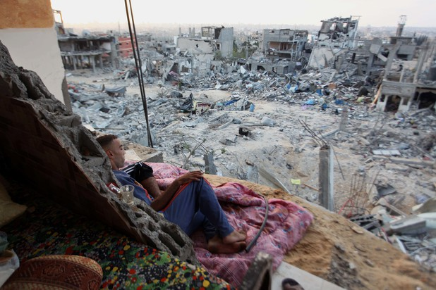 A Palestinian man lies down among a destroyed house after returning home in the Tufah neighbourhood in eastern Gaza City