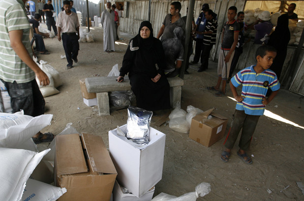 Palestinians wait to receive food supplies from a distribution centre of the United Nations Relief and Works Agency (UNRWA