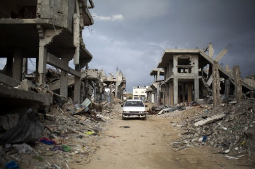 <p> Palestinians drive through a destroyed quarter of Al Shaaf area in Al Tuffah, east of Gaza City, March 21, 2015. Six month after the ceasefire that ended the Israeli 2014 summer offensive, 100,000 Palestinians are still displaced and many live in dire conditions. Rebuilding materials are scarce as the Gaza Strip face restrictions imposed by Israel.</p>