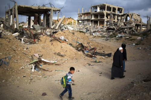 <p> Palestinians walk through a destroyed quarter of Al Shaaf area in Al Tuffah, east of Gaza City, March 21, 2015. Six month after the ceasefire that ended the Israeli 2014 summer offensive, 100,000 Palestinians are still displaced and many live in dire conditions. Rebuilding materials are scarce as the Gaza Strip face restrictions imposed by Israel.</p>