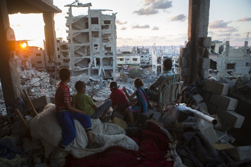 A Palestinian family sits in their destroyed home in a quarter in At-Tuffah district of Gaza city, which was heavily attacked during last Israeli offensive, Gaza city, September 21, 2014. During the seven-week Israeli military offensive, 2,131 Palestinians were killed, including 501 children, and an estimated 18,000 housing units have been either destroyed or severely damaged, leaving more than 108,000 people homeless.