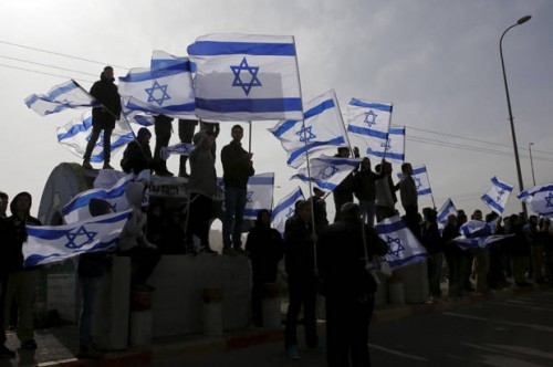 Israelis wave their national flag as a convey transporting the body of Dafna Meir, 38, passes on its way to a cemetery, near the West Bank Jewish settlement of Efrat January 18, 2016. Meir, a female resident of the West Bank settlement of Otniel, was stabbed to death in her home on Sunday when an assailant broke into her house and attacked her, the Israeli army and a local settlement official said. REUTERS/Ronen Zvulun - RTX22UYW